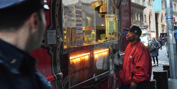A local man is checking out his food options at a food truck in Wall Street while a New York City police officer is looking at him.